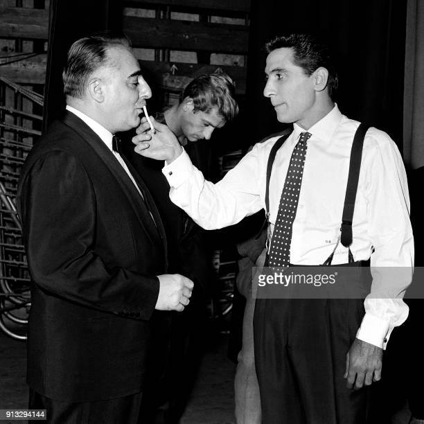 French singer Gilbert Becaud takes the cigarette of Bruno Coquatrix owner and manager of Paris Olympia in the wings of the music hall during his...