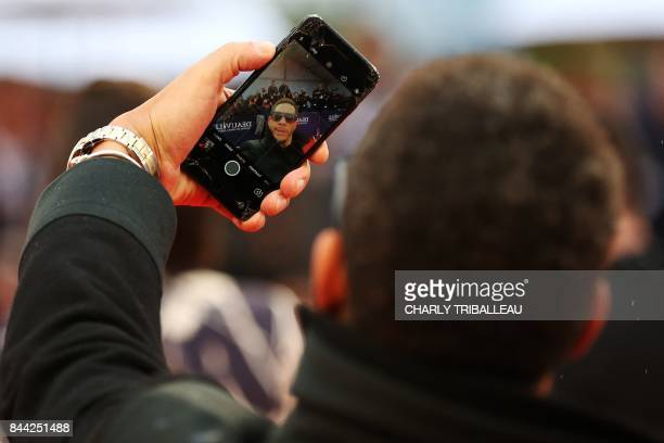 TOPSHOT French singer Joey Starr takes a photo on the red carpet before the screening of the movie Mother on September 8 2017 in the northwestern sea...