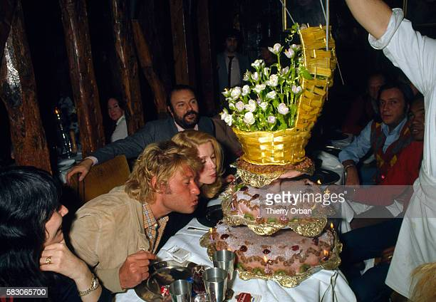 French singer Johnny Hallyday and French actress Catherine Deneuve blow out the candles on a birthday cake at the King's Club in Paris The two stars...