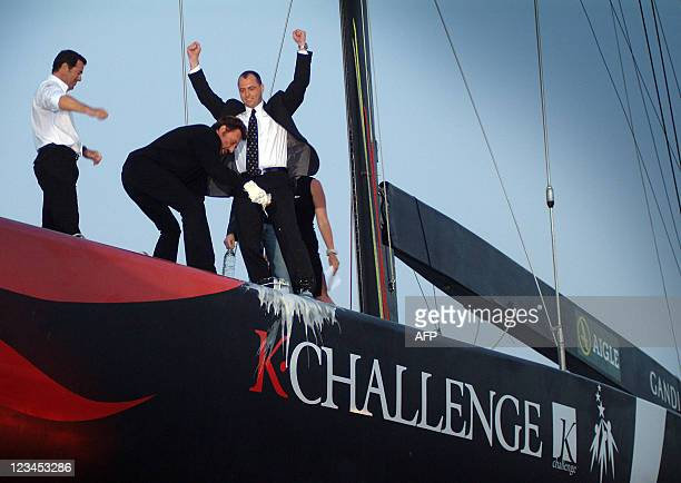 French Singer Johnny Hallyday breaks a champagne bottle during baptism of the new French ship for the America's Cup KCallenger at Gandia near...