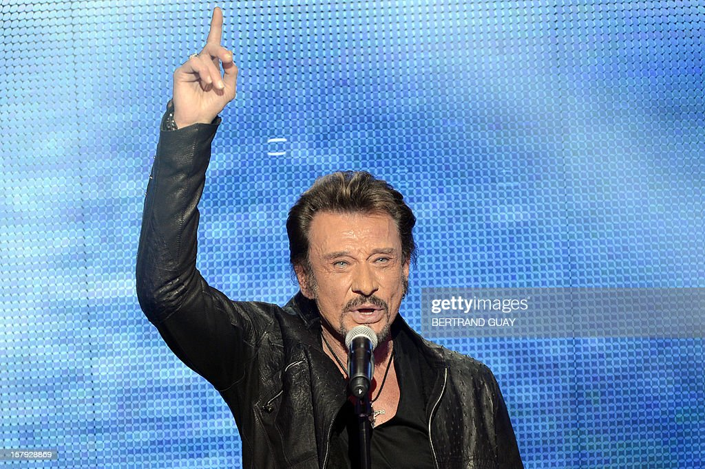French singer Johnny Hallyday performs on stage during the 26th Telethon, France's biggest annual fund-raising event broadcast on television during 30 hours, on December 7, 2012 in Saint-Denis, north of Paris. The event, aiming at collecting funds for research on genetic diseases such as myopathy, a neuromuscular disease, will run until December 8, 2012.