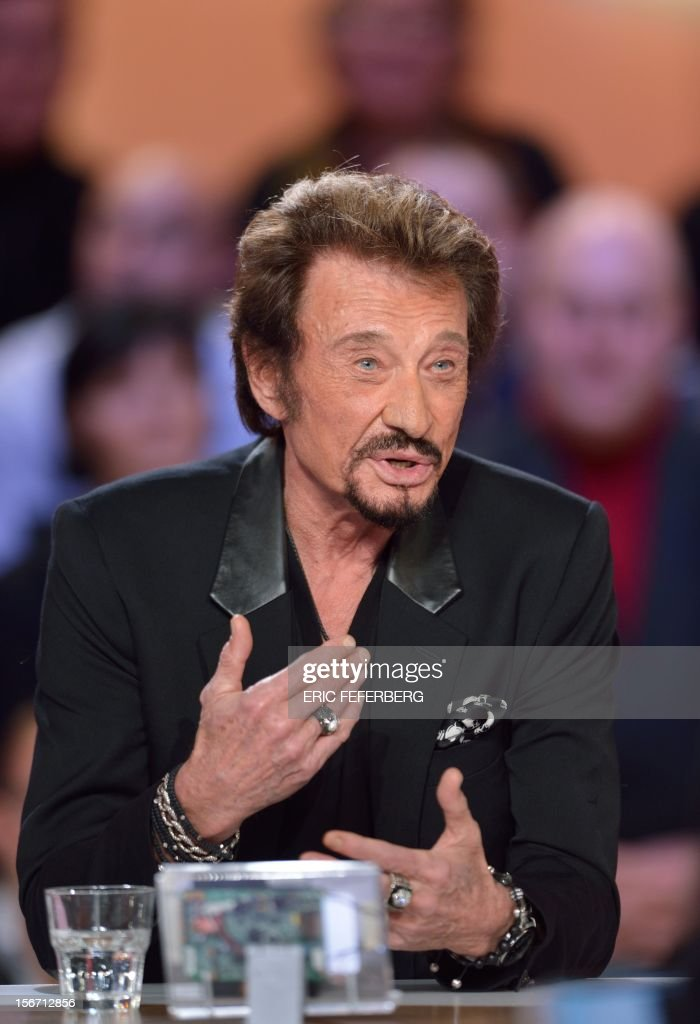 French singer Johnny Hallyday speaks as he takes part in the TV show 'Le grand journal' on a set of French TV Canal+, on November 19, 2012 in Paris, to present his new album entitled, 'The wait'. AFP PHOTO/ERIC FEFERBERG / AFP PHOTO / Eric Feferberg