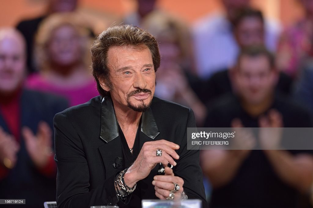 French singer Johnny Hallyday speaks as he takes part in the TV show 'Le grand journal' on a set of French TV Canal+, on November 19, 2012 in Paris, to present his new album entitled, 'The wait'.