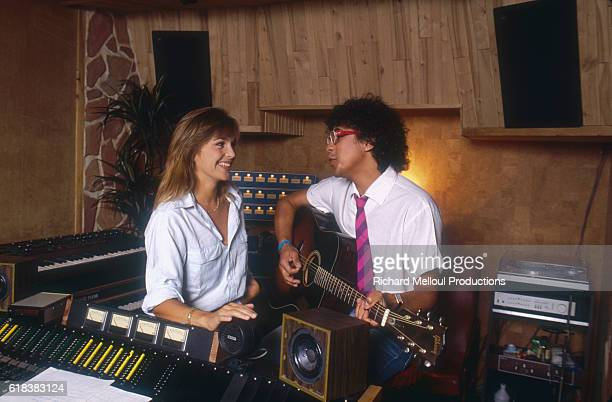 French singer Laurent Voulzy plays acoustic guitar in his home recording studio as actress Veronique Jannot listens.