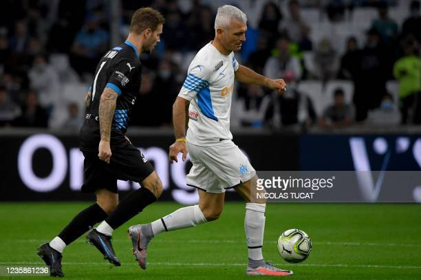 """French singer M Pokora fights for the ball with former Olympique de Marseille player Italian forward Fabrizio Ravanelli during the charity """"Heroes""""..."""