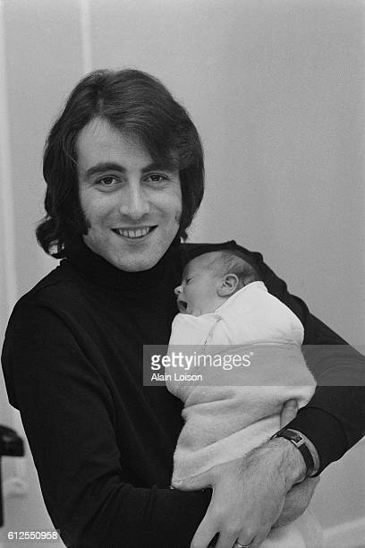 French singer Michel Delpech holds his newborn baby girl Garance whom he had with his wife Chantal Simon