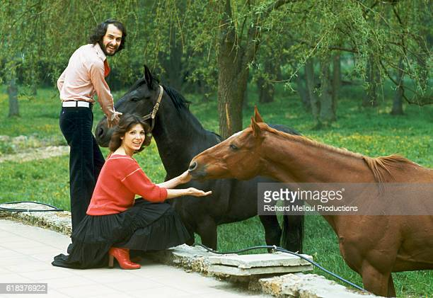 French singer Michel Fugain and his wife Stephanie pet horses on their estate. Michel Fugain was a popular singer who performed with the band Big...