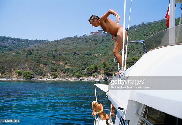 French Singer Michel Sardou dives nude from his boat while on vacation in StTropez France with his wife Babette