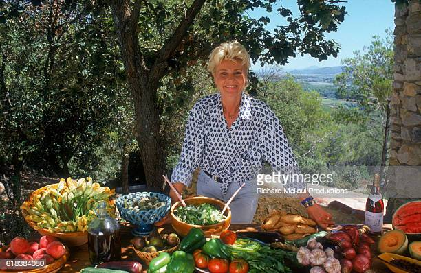 French singer Michele Torr stands before a table of fresh vegetables. She is preparing a book on Provencal cooking entitled, La Cuisine de Ma Mere.