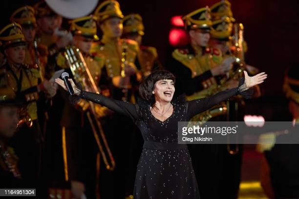 French singer Mireille Mathieu performs during the International Military Festival 'Sasskaya Tower' at the Red Square on August 30 2019 in Moscow...