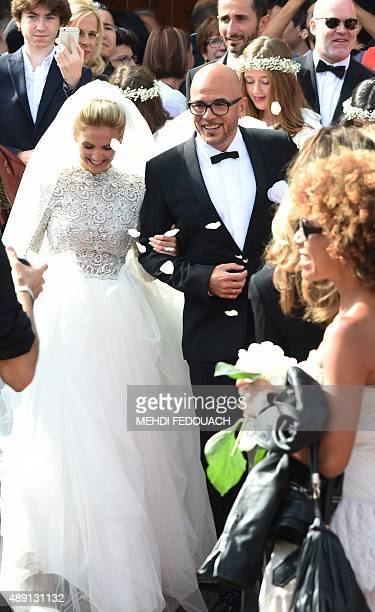French singer Pascal Obispo and model Julie Hantson leave Cap Ferret's church after their wedding on September 19 2015 AFP PHOTO / MEHDI FEDOUACH