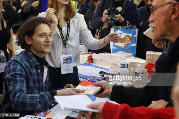 French singer Raphael Haroche signs his book during the 36th edition of the 'Foire du Livre de Brive' book fair on November 11 2017 in...