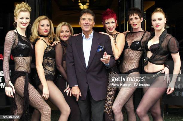 French singer Sacha Distel on the steps of the Aldephi Theatre in London's West End with the cast members from the musical 'Chicago' in which he will...