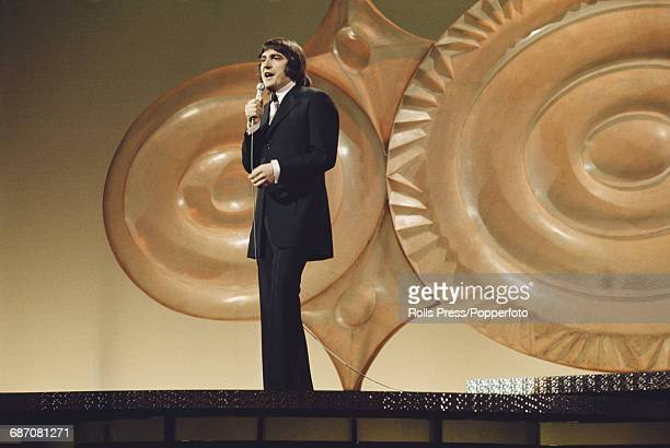 French singer Serge Lama performs the song 'Un jardin sur la terre' on stage for France in the 1971 Eurovision Song Contest at the Gaiety Theatre in...