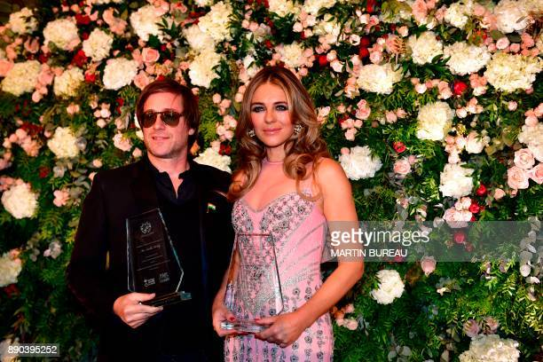French singer Thomas Dutronc and British actress Liz Hurley pose in Paris on December 11, 2017 during a charity dinner in honour of Indian...
