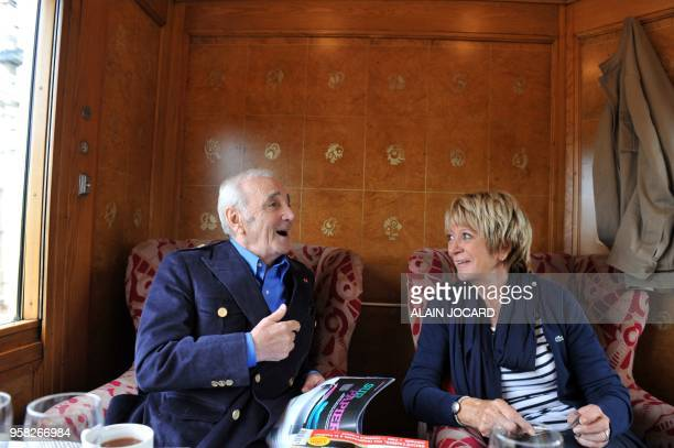 French singers Charles Aznavour and Alice Dona discuss on the OrientExpress train which brings them to ChanceauprèsLoches central France to attend...