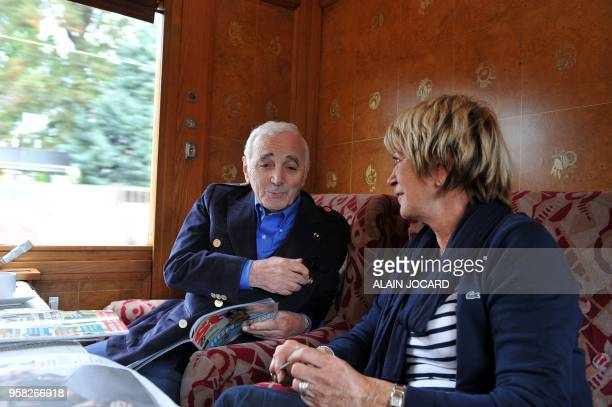 French singers Charles Aznavour and Alice Dona talk aboard the Orient Express train in Paris on August 28 2011 en route to the French central city of...