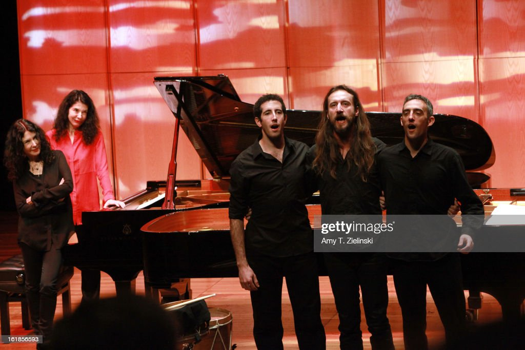 French sisters, concert pianists Katia Labeque (L) and Marielle Labeque (2nd-L) look on during a vocal performance by their percussionists (L-R) Jamixel Bereau, Xan Errotabehere and Thierry Biscary of Kalakan Trio after they performed together Ravel's 'Bolero' arrangement for duo piano as part of 'Imagine' family concerts programming at the Queen Elizabeth Hall on February 17, 2013 in London, England.