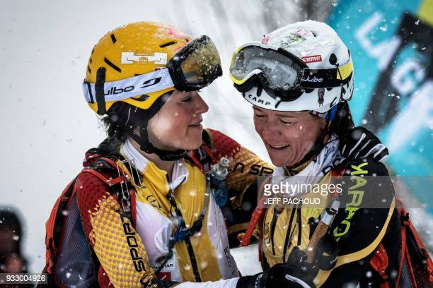 French skier Axelle Mollaret and her partner Italian skier Katia Tomatis celebrate as they cross the finish line to win on March 17 2018 the fourth...