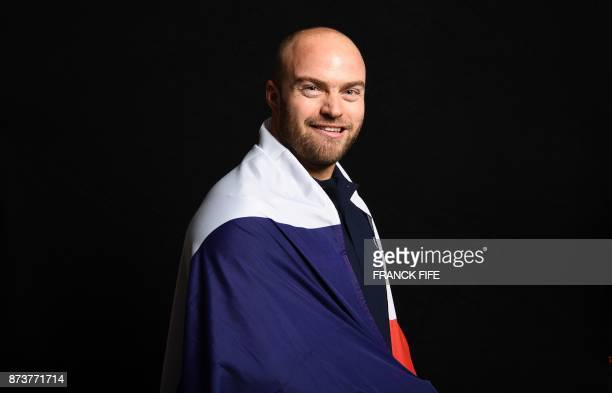French skier David Poisson poses with the French national flag during the presentation ceremony of the French delegation to the Olympic Games in...