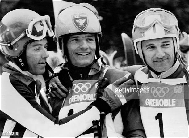 French skier JeanClaude Killy standing next to teammate Guy Perillat is congratulated by Swiss JeanDaniel Daetwyler in the finish area of the men's...