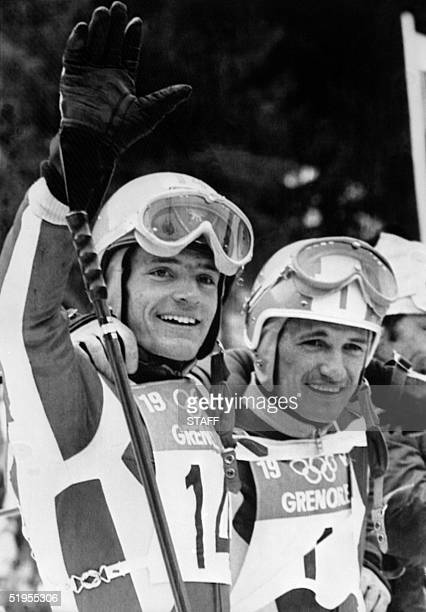 French skiers JeanClaude Killy waves to the crowd as he celebrates with teammate Guy Perillat 14 February 1968 in Chamrousse near Grenoble during the...