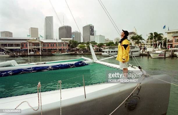 """French skipper Bruno Peyron looks up at storm clouds as he stands on one of the hulls of his 86-foot Catamaran """"Explorer"""" at a local marina in..."""