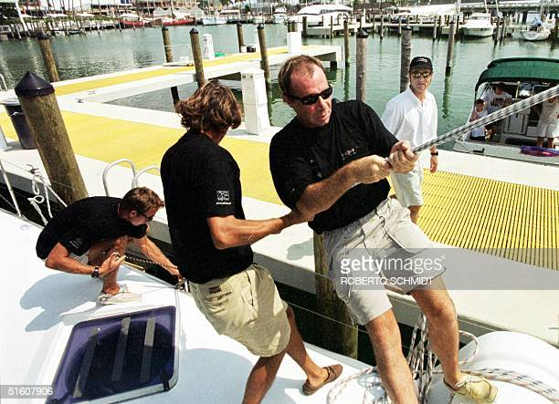 """French skipper Bruno Peyron watches as part of his crew readies his 86-foot catamaran """"Explorer"""" before leaving a local marina in downtown Miami 29..."""