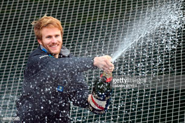 TOPSHOT French skipper Francois Gabart sprays champagne upon his arrival at the end of his solo around the world navigation on December 17 2017 in...