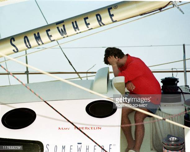 """French skipper Marc Thiercelin rest his head on his hand as he sits aboard his 60 foot yacht """"Somewhere"""" frustrated by weak and unfavorable winds..."""