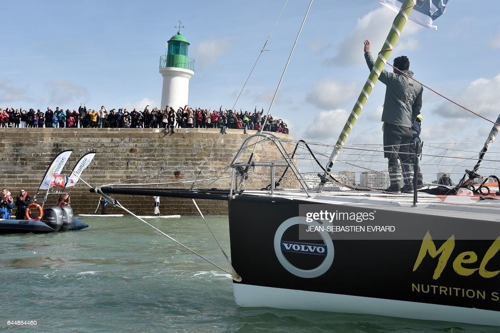 French skipper Romain Attanasio, placing 15th in the Vendee Globe around-the-world solo sailing race, celebrates aboard his Imoca 60 monohull 'Famille Mary-Etamine du Lys' on February 24, 2017 as he arrives in Les Sables-d'Olonne, western France. /