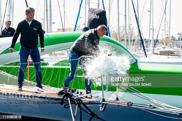 """French skipper Thomas Coville looks at Swiss South African explorer Mike Horn as he breaks a bottle of champagne on the the new multihull """"Sodebo..."""