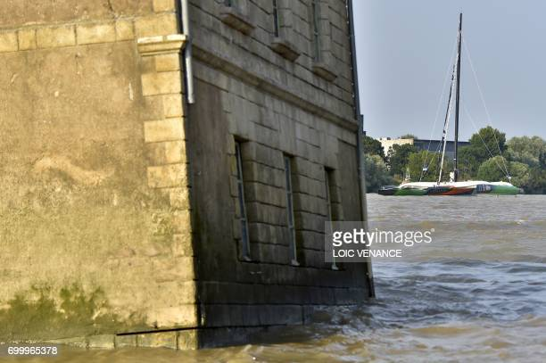 French Skipper Thomas Coville sails his Ultim multihull past the house in the Loire River by artist JeanLuc Courcoult off Coueron on June 22 2017...