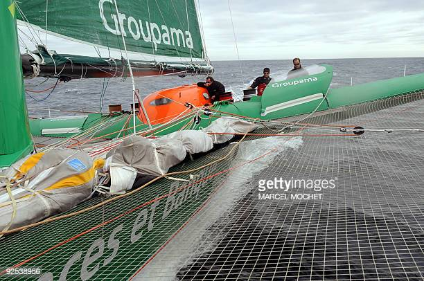 French skippers Franck Cammas Lionel Lemonchois and Thomas Coville maneuver on their maxitrimaran Groupama 3 during a training session at sea near...