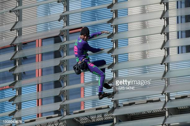 French skyscraper climber Alain Robert known as the French Spiderman climbs down the Agbar Tower in Barcelona on March 4 2020 as a symbolic action to...
