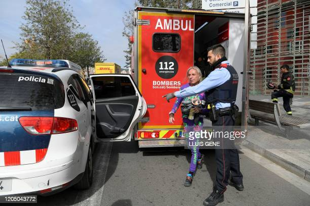 French skyscraper climber Alain Robert known as the French Spiderman is escorted by a member of the Catalan regional police force Mossos d'Esquadra...