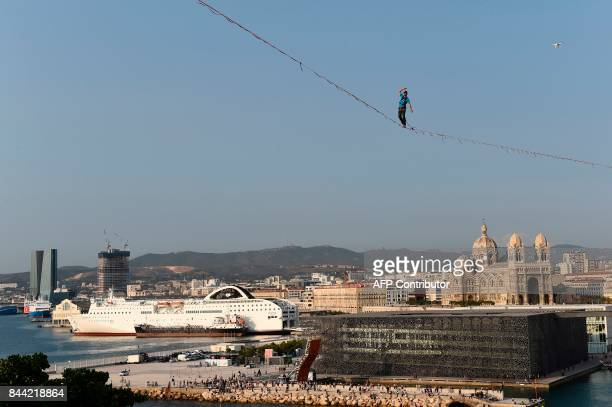 French slackliner Guillaume Rolland walks a distance of 250 meters across a highline slung at 50 meters over the VieuxPort in Marseille southern...