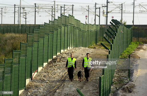 French SNCF railway police patrol a freight terminal September 12, 2002 in Calais, France. An increase in patrols and miles of new fencing has...