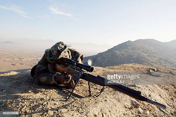 A French sniper from 92th Infantry Regiment Clermont Ferrand equipped with a FR F2 rifle aims at the target 13 November 2002 from his position near...