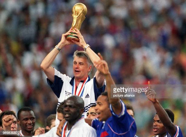 French soccer coach Aime Jacquet cheers and laughs with his players while he holds the World Cup trophy in his hands after the 1998 World Cup final...