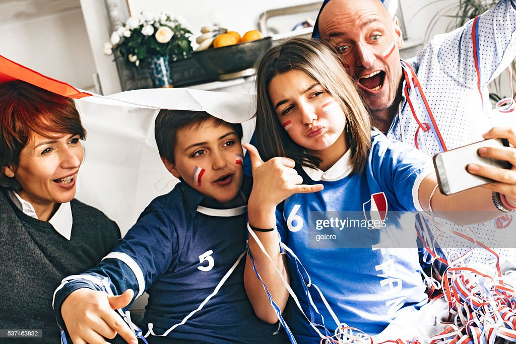 french soccer fan family  taking selfie with smartphone indoor : Stock Photo