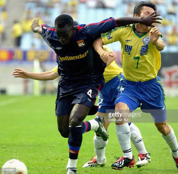 French soccer team Olympique Lyonnais's player Michael Essien fights for ball with South Korean team Seongnam Ilhwa's player Shin Taeyong during...