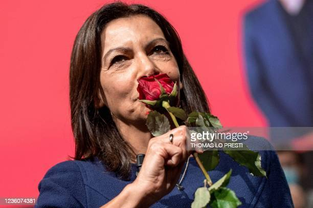 French Socialist Party candidate for the April 2022 presidential election Anne Hidalgo smells her party's emblem, a rose, at the end of her speech...