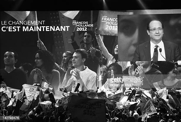French Socialist Party 's candidate for the 2012 presidential election Francois Hollande arrives on stage to give a speech during a campaign meeting...