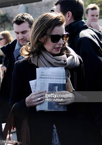 French Socialist Party 's presidential candidate companion, Valerie Trierweiler holds a newspaper walking upon her arrival at Marignane airport,...