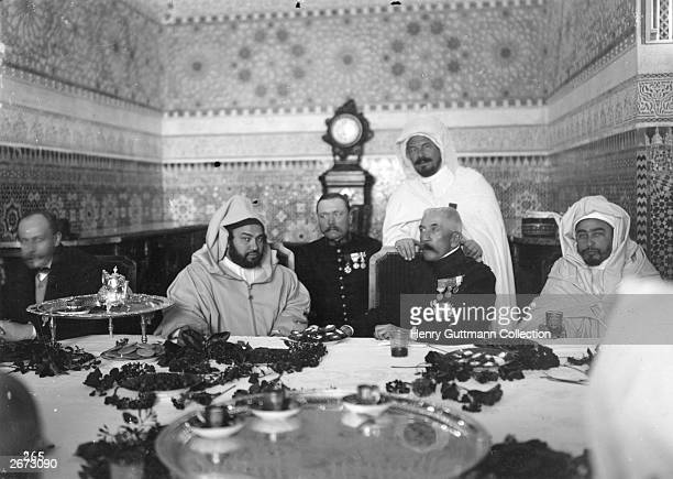 French soldier and colonial administrator Marshal Louis Hubert Gonzalve Lyautey, dining with Sultan Mulai Yusuf at the Sultan's table during the war...