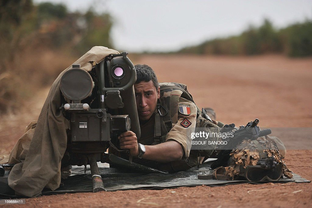 A French soldier deployed in Diabaly lays with a Milan ant-tank missile launcher at the forward posiotion near Diabaly on January 22, 2013. Italy said Tuesday it will send three planes to Mali to help support French and Malian troops battling Islamist rebels after parliament gave the green light for a two- to three-month logistical mission. AFP PHOTO / ISSOUF