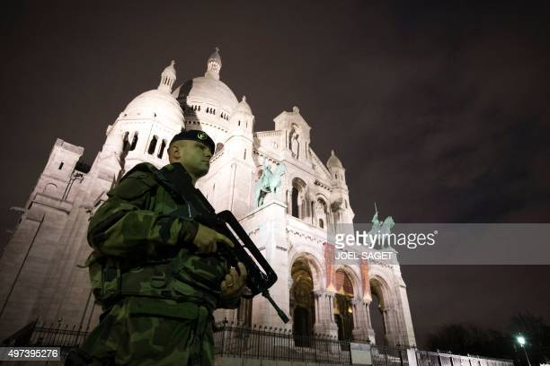 A French soldier enforcing the Vigipirate plan France's national security alert system patrols in front of the Sacre Coeur Basilica on November 16...