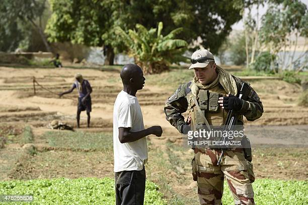 A French soldier from Operation Barkhane an antiterrorist operation in the Sahel speaks with a man at a vegetable garden near the banks of the Niger...