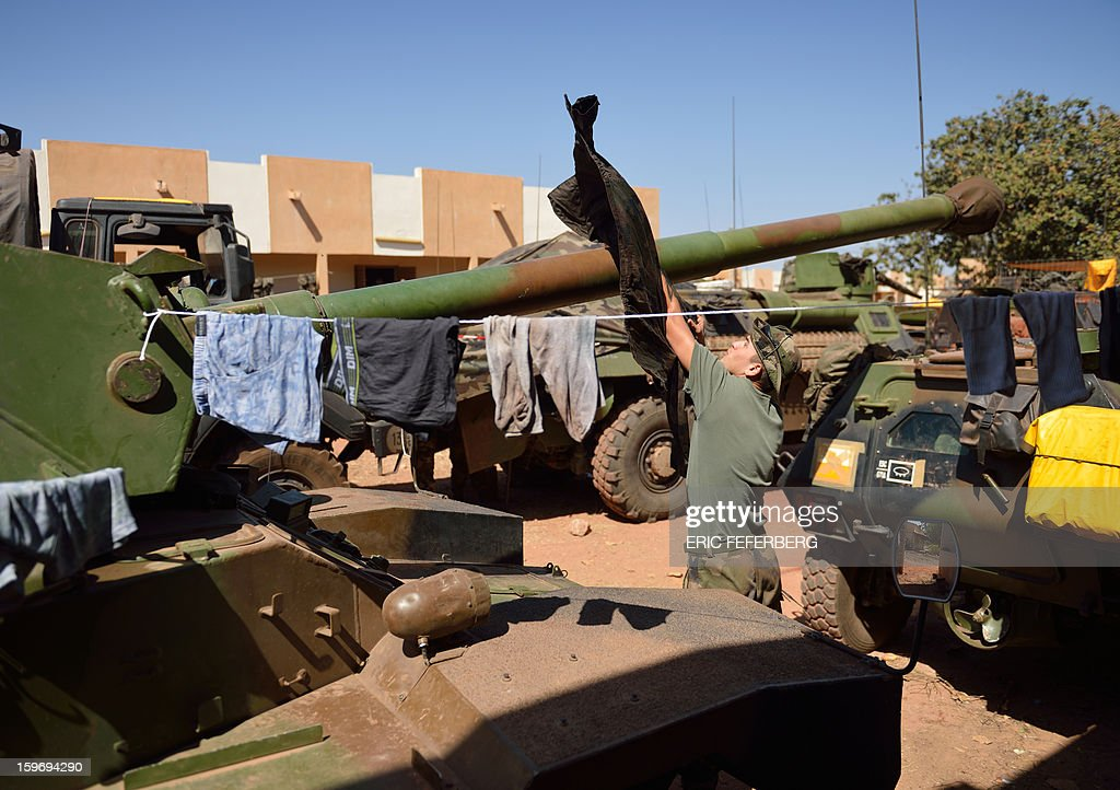 A French soldier from the 21st Rima hangs laundry on the barrel of a Sagaie tank, at the Malian army 101 airbase, where French troops are stationed, on January 18, 2013, near Bamako. France now has 1,800 troops on the ground in Mali, inching closer to the goal of 2,500 it plans to deploy in its African former colony, Defence Minister Jean-Yves Le Drian said today. That was 400 more than a day earlier, said the minister as he met with French special forces in the western port of Lorient. The troops have been sent to help the Malian army regain control of the north from Islamist groups.